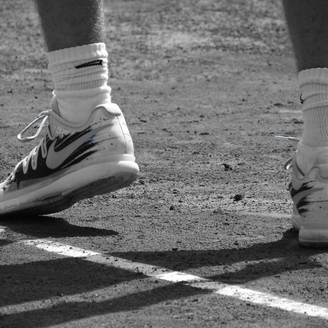 An image of a tennis player's feet at the service line - Moreno Osteopathy, you're in good hands