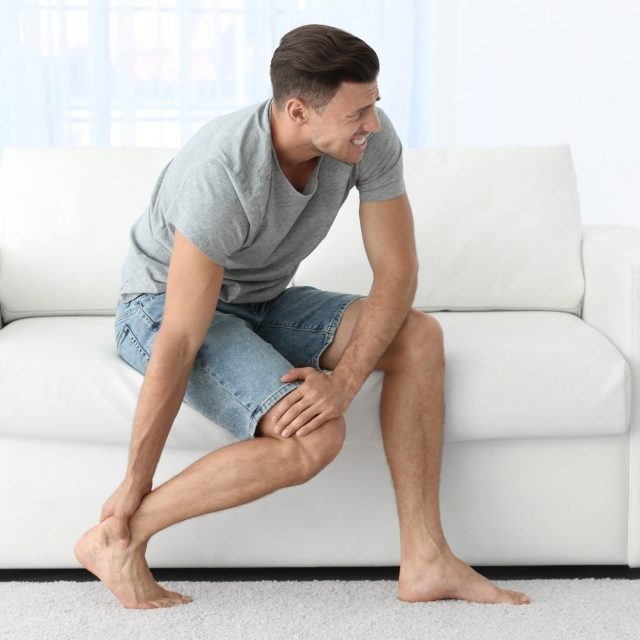 Young,Man,Suffering,From,Leg,Pain,At,Home